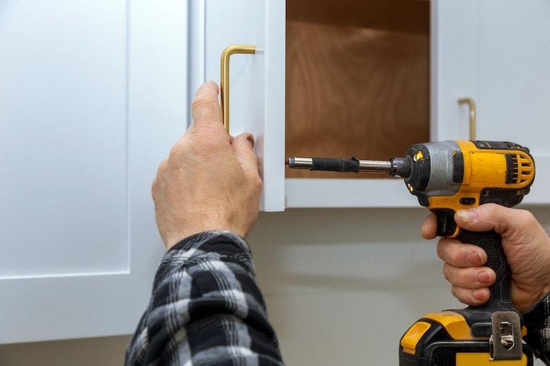 man replacing kitchen cabinet hardware